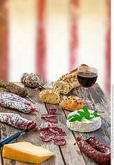 French snacks with wine - various types of cheeses  bread   dry suassages  charcuterie  red vine on a gray background. . Food background over timbered wall