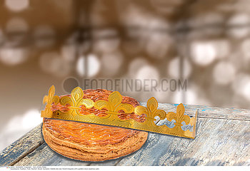 Galette des rois  french kingcake with a golden crown  on wooden table  epiphany cake against blury light