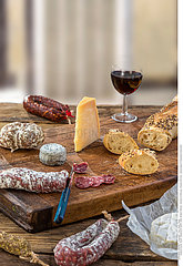 French snacks with wine - various types of cheeses  bread   dry saussages  charcuterie  red vine on a gray background.
