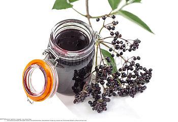 Elderberry Jam. Jar of homemade elderberry confiture and fresh fruits on white background
