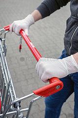 Berlin  Deutschland - Haende mit Einmal-Handschuhen am Griff eines Einkaufswagens vor einem Supermarkt