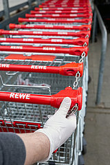 Berlin  Deutschland - Hand mit einem Einmal-Handschuh am Griff eines Einkaufswagens vor einem Supermarkt