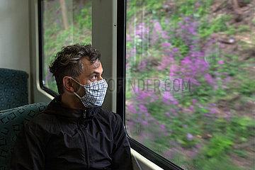 Berlin  Deutschland - Mann mit Schutzmaske in der Berliner S-Bahn