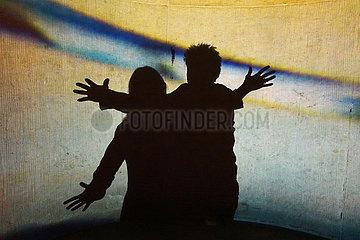 Berlin  Deutschland  Silhouette: Mann und Frau laufen mit offenen Armen aufeinander zu