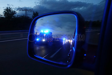 Schoenefeld  Deutschland  Rettungswagen auf Einsatzfahrt im Rueckspiegel eines PKW