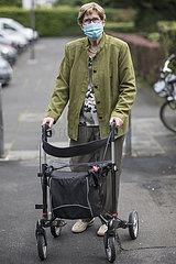 Seniorin mit Rollator und Mundschutz