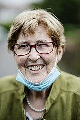 Seniorin mit Maske unter dem Kinn lachend  Portrait