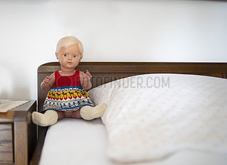 Alte Puppe sitzt auf einem Bett