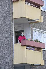 Seniorinmit Mundscutz auf Balkon im Seniorenwohnheim