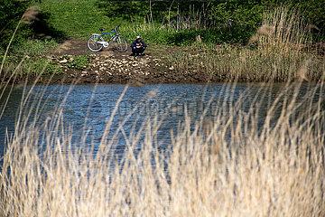 Deutschland  Bremen - Junger Mann mit Fahrrad am Ufer des Flusses Lesum  Bremen-Nord
