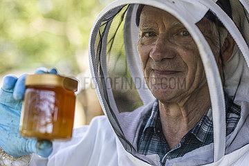 Imker hält ein Glas Honig in der Hand