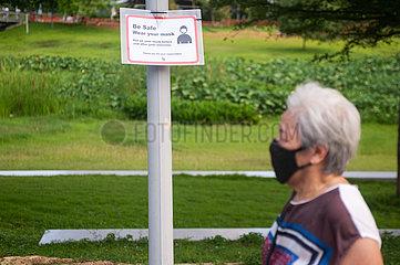 Singapur  Republik Singapur  Frau mit Mundschutz neben Hinweisschild zur Maskenpflicht im Freien
