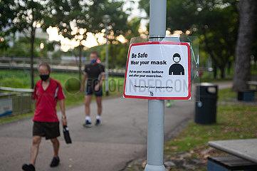 Singapur  Republik Singapur  Mann mit Mundschutz neben Hinweisschild zur Maskenpflicht im Freien