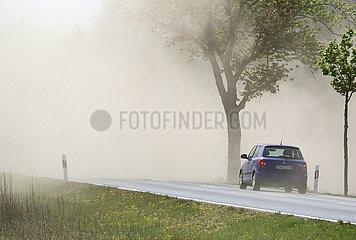 Doebrichau  Deutschland  PKW faehrt auf einer Landstrasse durch eine bei der Feldarbeit entstandene Staubwolke