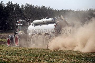 Doebrichau  Deutschland  Staubwolke entsteht beim Duengen eines trockenen Feldes