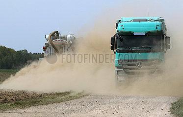 Doebrichau  Deutschland  LKW faehrt durch eine bei der Feldarbeit entstandene Staubwolke