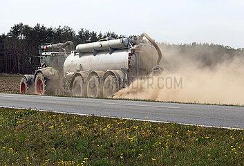 Doebrichau  Deutschland  Staubwolke entsteht beim Duengen eines trockenen Feldes an einer Landstrasse