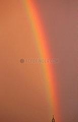 Berlin  Deutschland  Regenbogen am Abend ueber einem Kirchturm