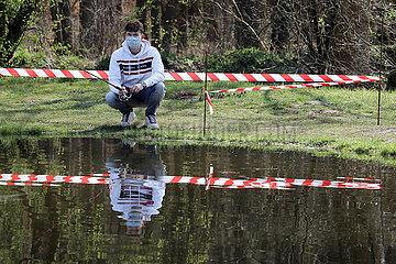 Kleinwall  Deutschland  Teenager fischt in Zeiten der Coronakrise mit Mundschutz an einem Angelteich