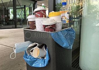 Berlin  Deutschland  Leere Kaffeebecher  Getraenkeflaschen und Mund-Nasen-Schutz ragen aus einem ueberfuelltem Muelleimer
