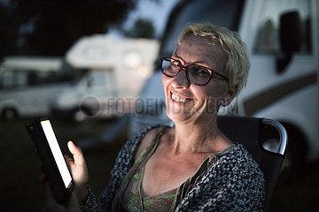 Camperin mit Smartphone auf Wohnmobilstellplatz