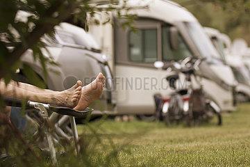 Füße eines Urlaubers auf einer Liege auf einem Wohnmobilplatz