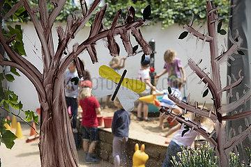 spielende Kinder im Kindergarten  Blick durch Fenster