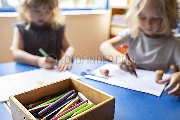 Kinder malen mit Buntstiften im Kindergarten