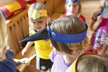 Kinder mit Masken proben für eine Aufführung in der Kindertagesstätte
