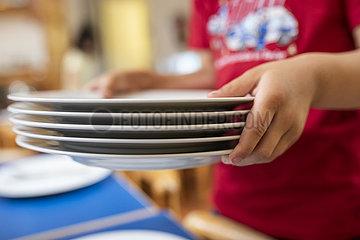 Junge im Kindergarten mit Tellern in der Hand deckt den Tisch