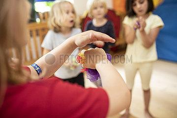 Kinder mit bunten Tüchern im Kindergarten