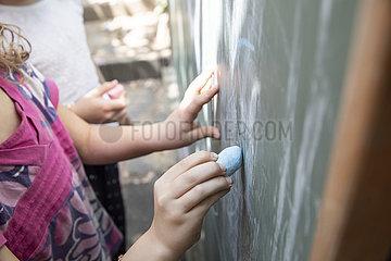 Kinder malen mit Kreide auf einer Tafel im Kindergarten