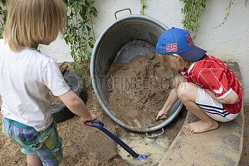 Kinder spielen mit Sand im Sandkasten