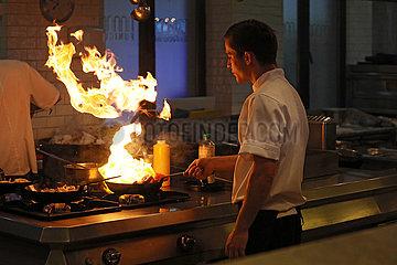 Tiflis  Georgien  Koch flambiert Essen in einer Pfanne