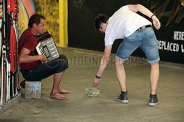 Tiflis  Georgien  Passant gibt einem Strassenmusikanten Geld