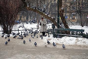 Krakau  Polen  Seniorin laeuft im Winter durch eine Parkanlage mit vielen Tauben