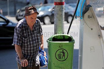 Tiflis  Georgien  alter Mann steht auf der Strasse neben einem Abfalleimer