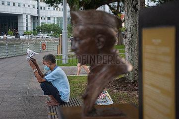 Singapur  Republik Singapur  Mann mit Mundschutz liest waehrend Lockdown Zeitung entlang der Uferpromenade