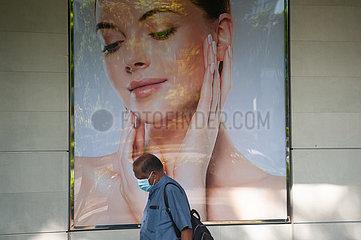 Singapur  Republik Singapur  Mann mit Mundschutz geht an einer Werbeflaeche vorbei