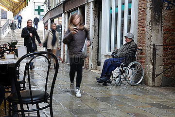 Venedig  Italien  alter Mann sitzt im Rollstuhl von Passanten ignoriert auf einer Strasse