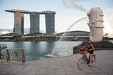 Singapur  Republik Singapur  Frau mit Mundschutz im Merlion Park und Marina Bay Sands Hotel im Hintergrund