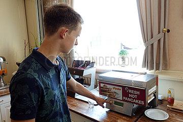 Langenhagen  Deutschland  Junge bereitet sich zum Fruehstueck Pancakes mit einem Automaten zu