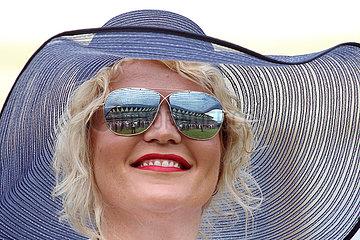 Ascot  Grossbritannien  Frau mit Hut und verspiegelter Sonnenbrille auf der Galopprennbahn