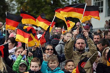 Hoppegarten  Deutschland  Menschen schwenken am Tag der Deutschen Einheit Nationalfahnen
