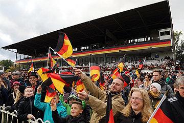 Hoppegarten  Deutschland  Menschen schwenken am Tag der Deutschen Einheit Nationalfahnen vor der Tribuene der Galopprennbahn