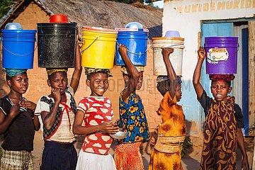 Kinderarbeit Wasserbeschaffung: Maedchen schleppen Wassereimer auf dem Kopf