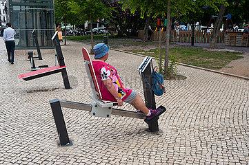Lissabon  Portugal  Frau auf Fitnessgeraet in einem Fitnessparcour am Strassenrand