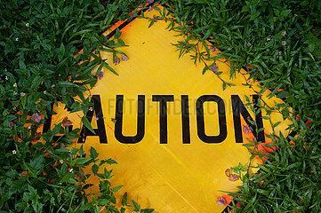 Singapur  Republik Singapur  Warnschild mit Aufschrift Caution (Vorsicht) liegt am Strassenrand im Gras
