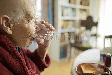 Alte Frau trinkt Wasser