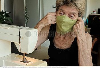 A volunteer makes masks